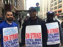 (From l.) IBEW Local 3 members Philip Sclafani, Jesus de la Cruz and Ayobami Ojedapo walk the picket line Friday outside Charter Communications' E. 23rd St. headquarters.